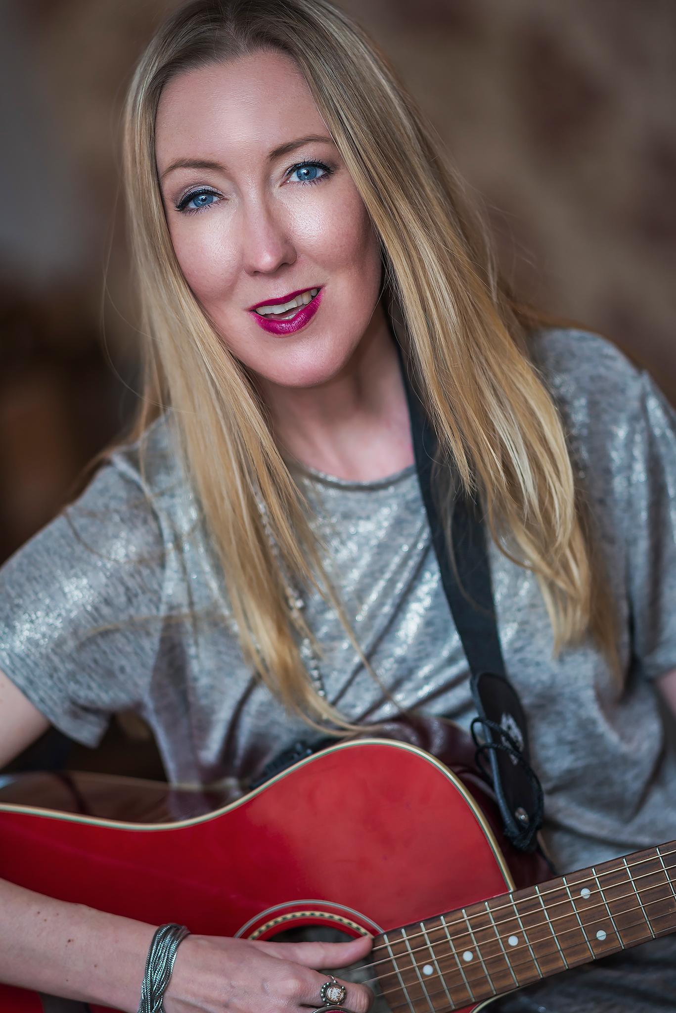 Kajsa Larsson som spelar på Café Hängmattan 5 september, sitter med sin röda gitarr. Ler mot kameran. Trubadurkväll i Strängnäs 16 augusti och 12 + 27 juli