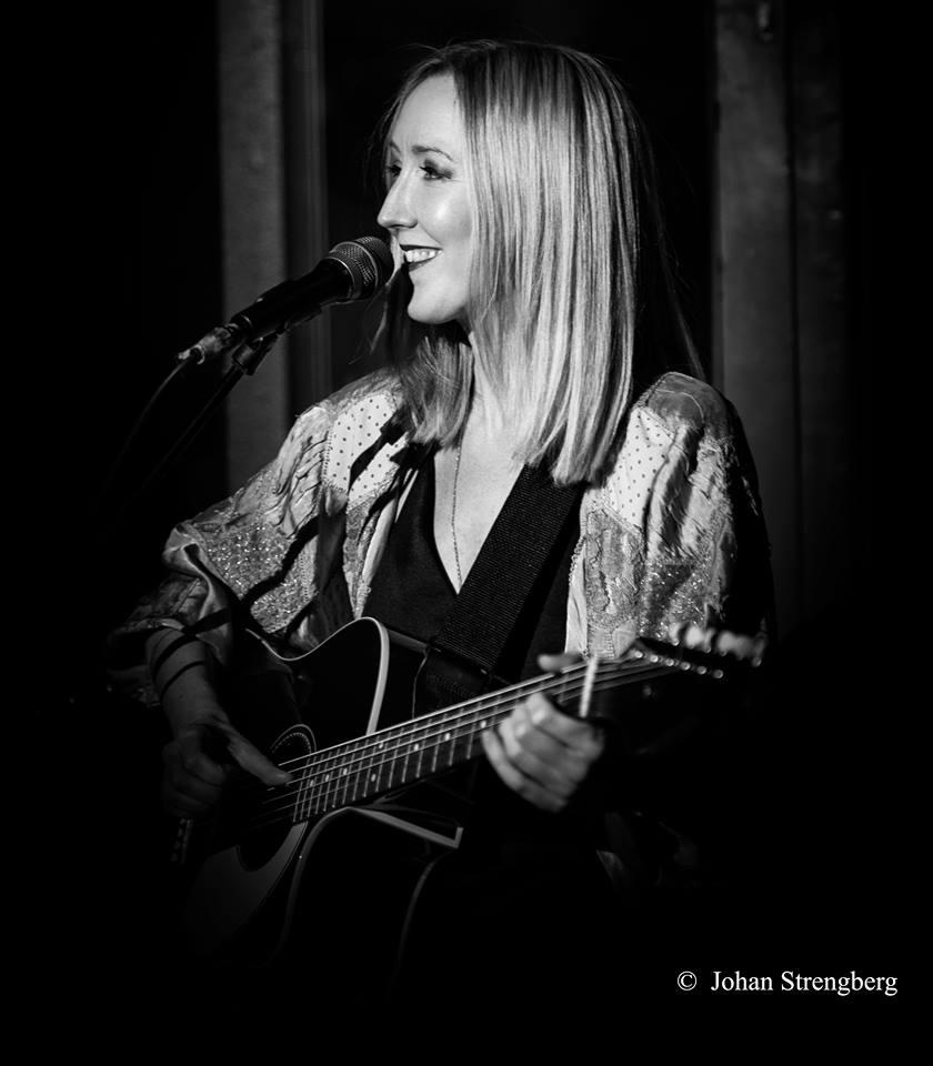 Kajsa Larsson håller i en gitarr, ler